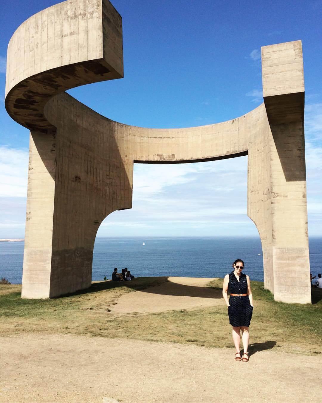 Standing in front of Elogio del horizonte sculpture overlooking the Bay of Biscay in Gijon, Spain