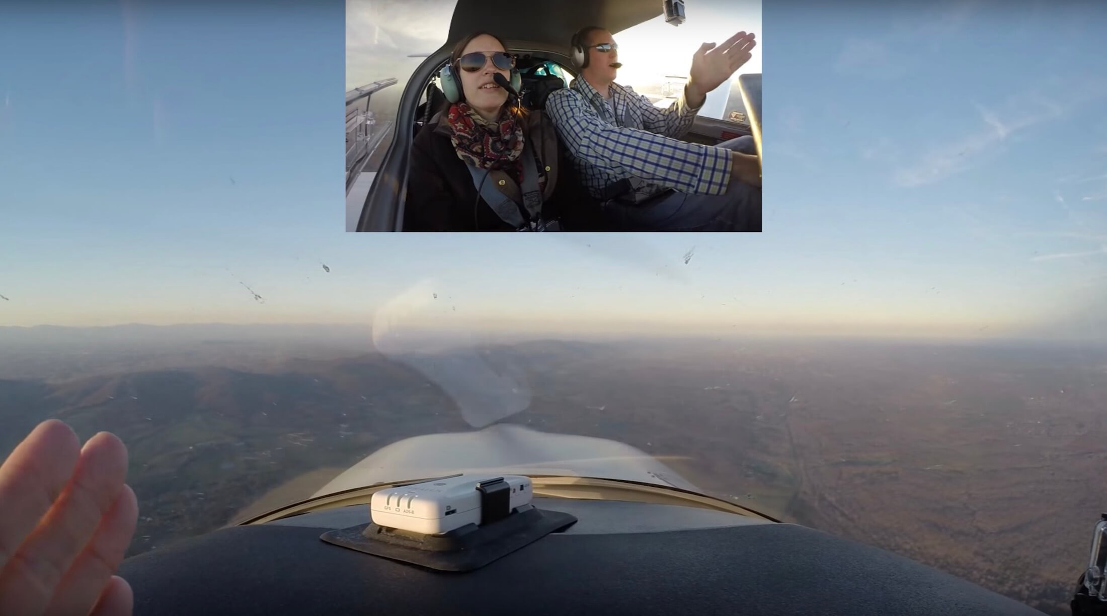 Me flying a plane while pilot Chas tells me direction to go in, inset over an inflight view of mountains through the windscreen.